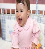 Luísa sorrindo usando o vestidinho rosa da Lione.